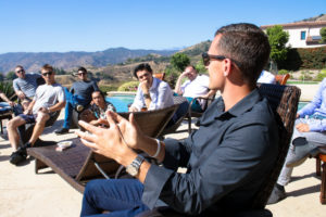 Austin sitting by a pool with a business coaching class he's leading.
